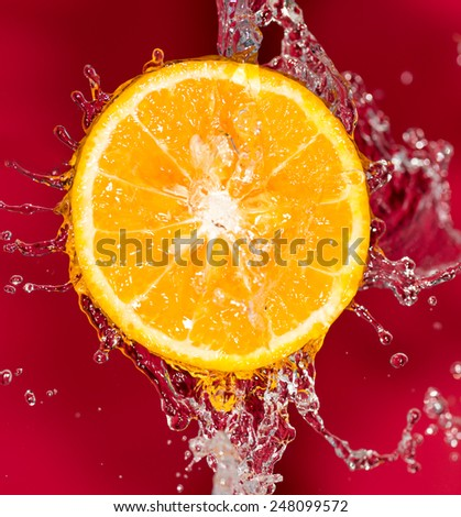 orange in water on a red background background - stock photo
