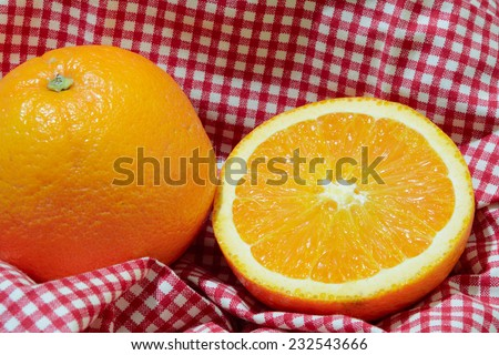 Orange is placed on the fabric in the picnic basket - stock photo