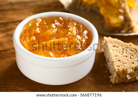 Orange jam in small bowl on wood with bread on the side, photographed with natural light (Selective Focus, Focus one third into the jam)  - stock photo