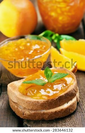 Orange jam on toast over wooden table - stock photo