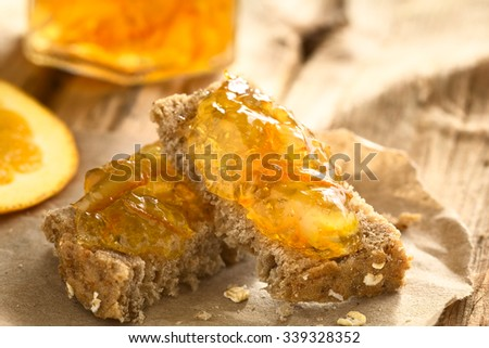 Orange jam on wholegrain bread slices, photographed with natural light (Selective Focus, Focus on the first orange peels on the bread pieces)