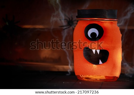 Orange jar decorated as a Halloween monster with a scary Cyclops face standing on rustic wooden shelves festooned in spiders and cobwebs on a shadowy background with copyspace - stock photo
