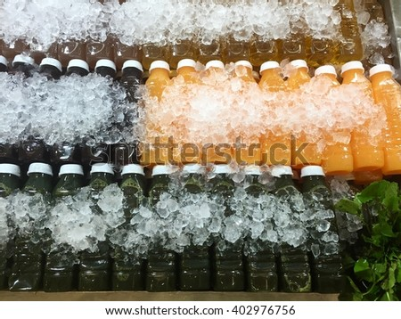 Orange juice and Asiatic water in bottles with ice - stock photo