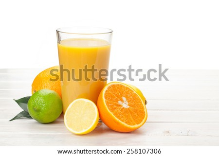 Orange juice and citrus fruits on white wooden table