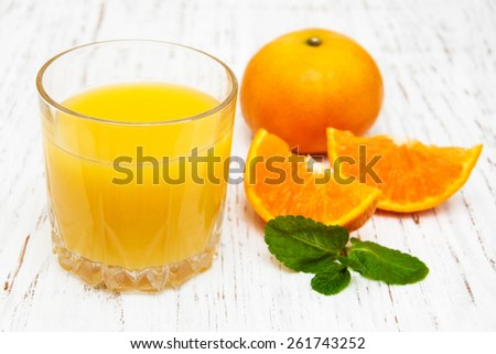 Orange juice and fresh oranges on a wooden background