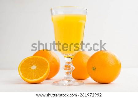 Orange juice and oranges on the white background - stock photo