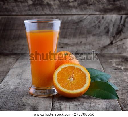 Orange juice glass and fresh oranges on wood - stock photo