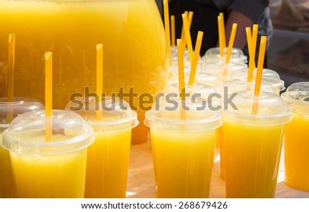 Orange juice in fast food closed cups - stock photo