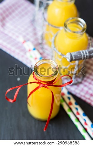 Orange juice in glass bottle,  on wooden background
