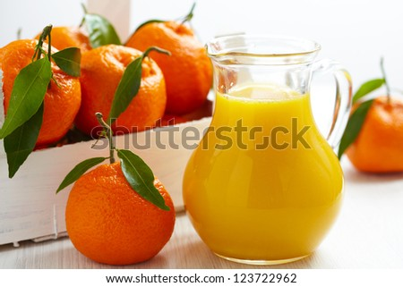 Orange juice in pitcher and tangerines with leaves in wooden box - stock photo
