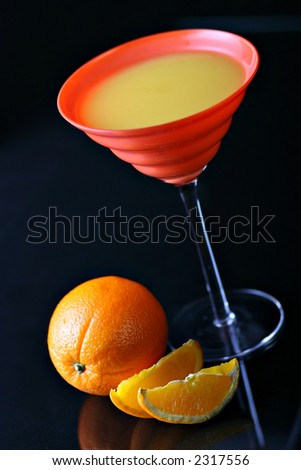 Orange juice in red glass with oranges on background, on black, with reflections - stock photo