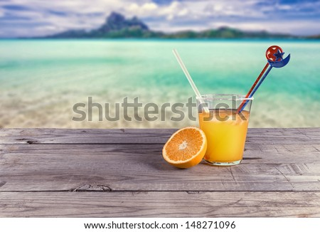 orange juice on the table with a sea view - stock photo