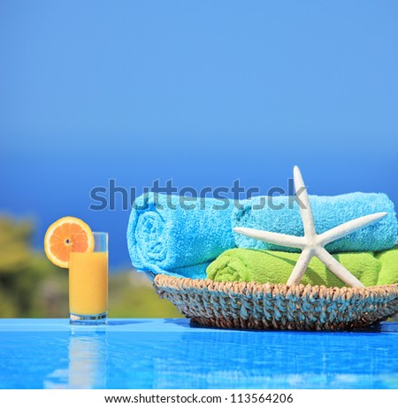 Orange juice, starfish and rolled up towels next to a swimming pool - stock photo