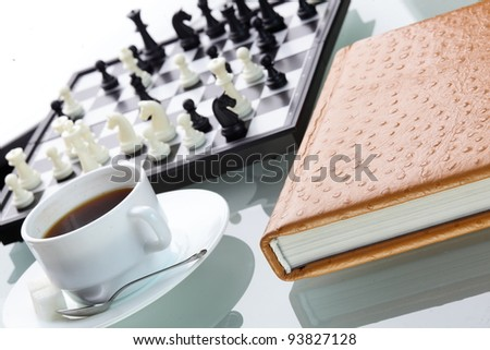 orange leather book on bright background and chess - stock photo