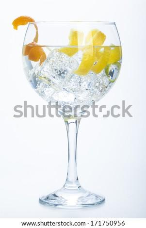 orange lemon and lime gin tonic isolated over white background - stock photo