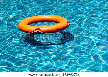 Orange life buoy is splashing with clear blue water in swimming pool, for the emergency case, use as the background and left the space for text - stock photo