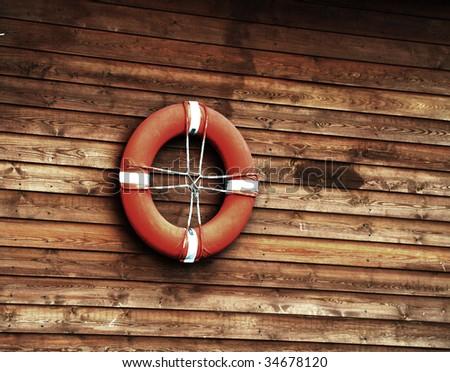 orange life buoy on a timber wall - stock photo
