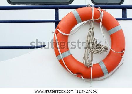 Orange lifebuoy and old rope hanging on a boat - stock photo