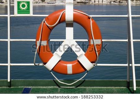 Orange lifebuoy on deck railing of passenger ship - stock photo