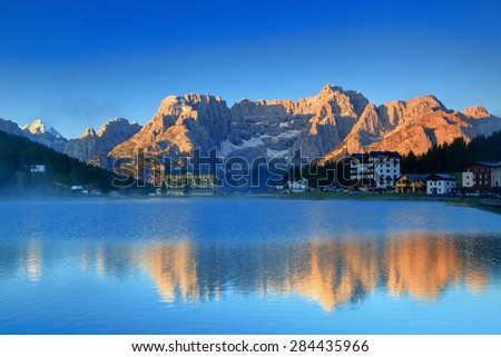 Orange light illuminates Sorapis Mountains reflected by Misurina lake, Dolomite Alps, Italy - stock photo