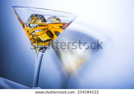 Orange liqueur into a martini glass. Multicolored reflections on the background. - stock photo