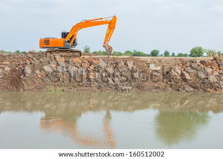 orange loaders are dredging canals and shadow in water - stock photo