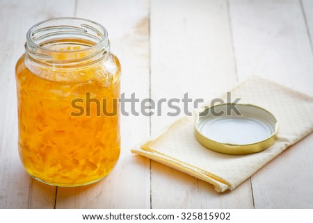 Orange marmalade jam in glass on wood background - stock photo