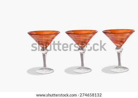 Orange martini cocktail blown glasses on a white background
