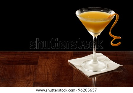 orange martini garnished with a twist isolated on black - stock photo