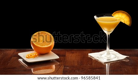 orange martini on a bar top garnished with an orange slice and fresh orange on the side - stock photo