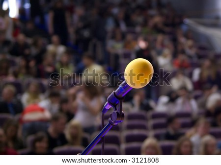orange microphone on the stage and audience - stock photo