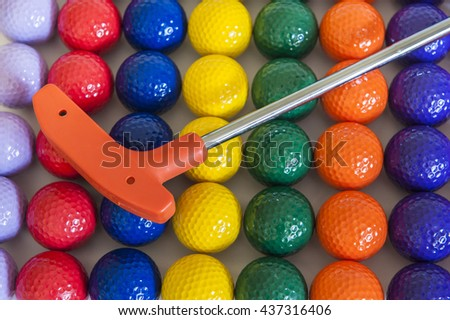 Orange mini golf club with a variety of colorful golf balls