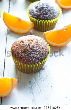 Orange muffins at the white wooden table and sli?ed oranges - stock photo