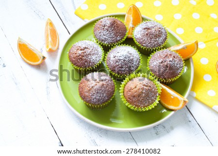 Orange muffins on the big green plate - stock photo