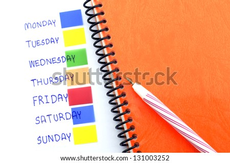 orange notebook red pen and post it monday to sunday - stock photo