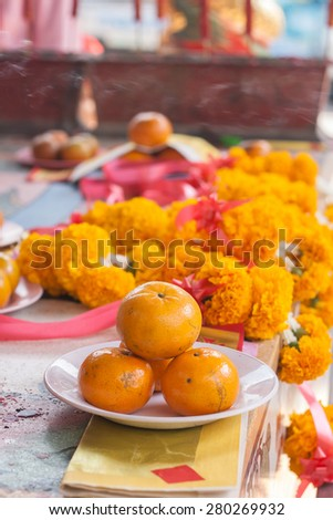 Orange on dish in chinese shrine for making merit in chinese new year with marigold flower background. - stock photo