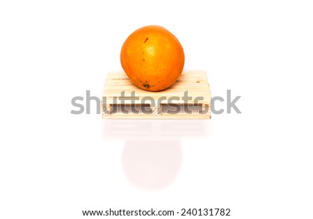 orange on wood pallet ready for shipment - conceptual photo with shadow and reflection on white background - stock photo