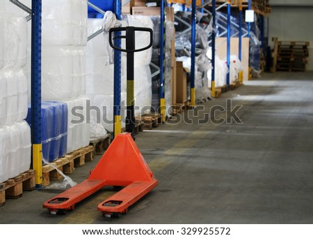 Orange pallet truck for package in the warehouse