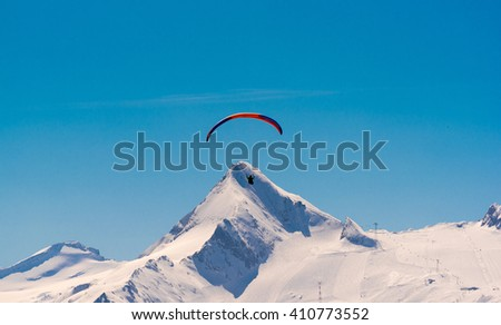 orange paraglider in front of kitzsteinhorn, austrian alps - stock photo