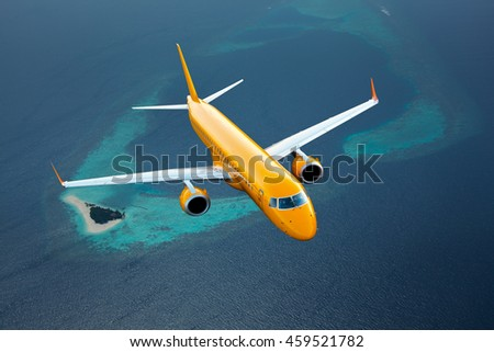 Orange passenger airplane. Aircraft flies over the deep-blue ocean and Maldives island. - stock photo