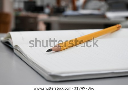 Orange pencil on the notebook.