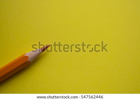 orange pencil on yellow background