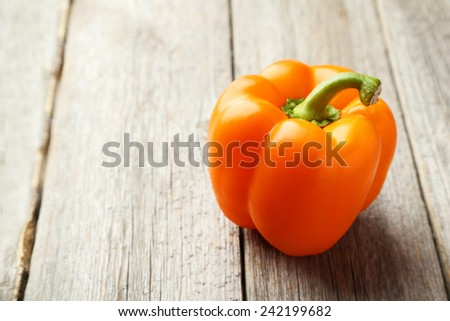 Orange pepper on grey wooden background - stock photo