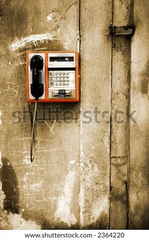 Orange phone on monochrome grunge background - stock photo
