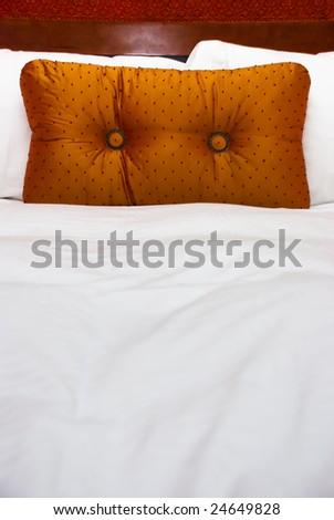Orange pillow on white linen sheets against wood headboard. - stock photo