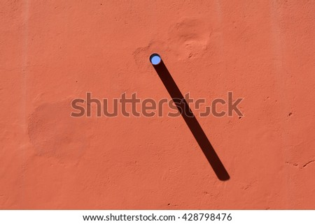 Orange plaster wall with a single pipe protruding - stock photo