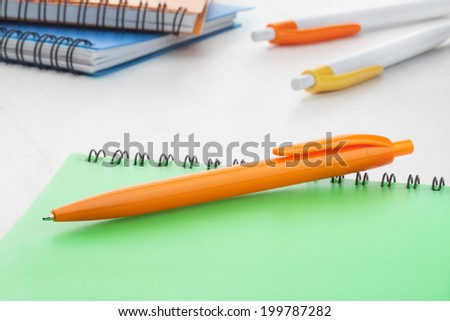 Orange plastic ball pen with green notebook at the back office supplies on white background. - stock photo