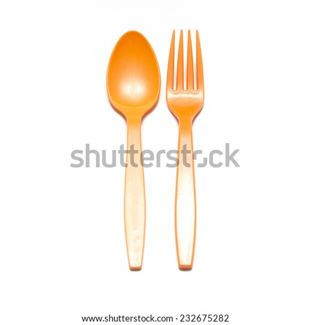 orange plastic spoon and fork on a white background - stock photo