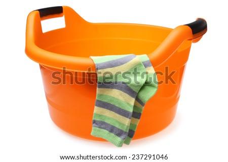 Orange plastic wash bowl with striped socks on white background - stock photo