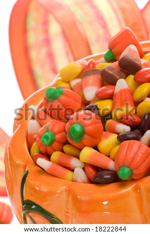 Orange pumpkin filled with delicious Halloween candies - stock photo